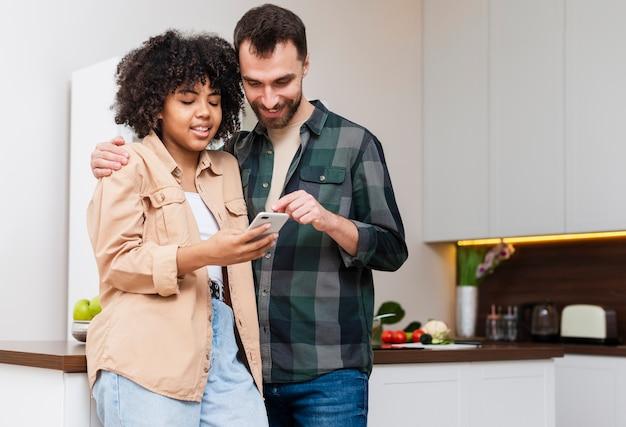Heureux homme et femme à la recherche au téléphone