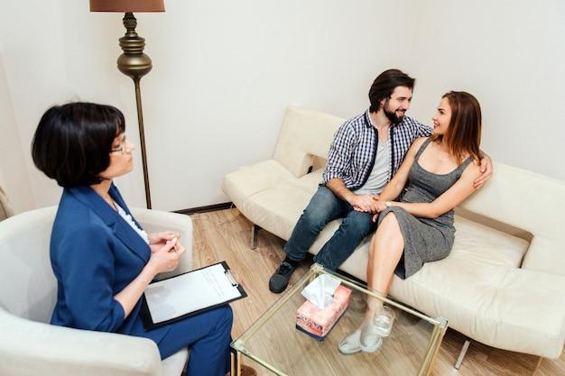 Heureux homme et femme sont assis ensemble et se regardent. leur vue est pleine d'amour et de soutien. ils se tiennent par la main. le docteur les regarde.