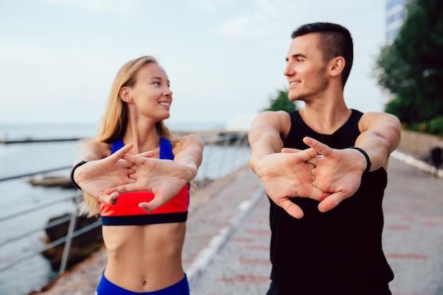 Heureux homme et femme souriante faisant des exercices d'étirement pour les bras pendant l'entraînement