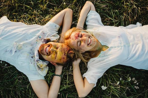 Heureux homme et femme avec des visages dans des peintures colorées se trouvent sur la pelouse verte