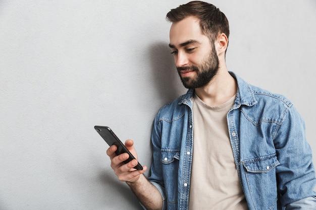 Heureux homme gai portant chemise isolé sur mur gris, à l'aide de téléphone mobile