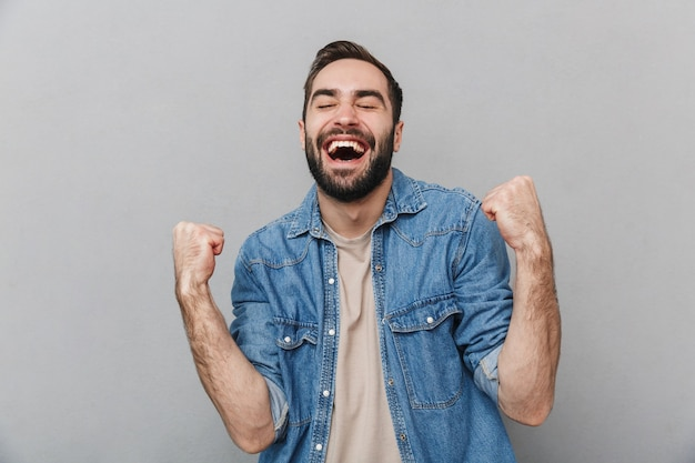 Heureux homme gai portant chemise isolé sur mur gris, célébrant le succès