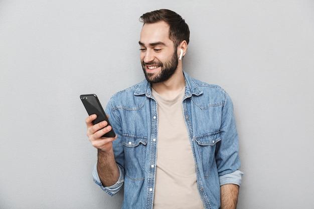 Heureux homme gai portant chemise isolé sur mur gris, portant des écouteurs, à l'aide de téléphone mobile