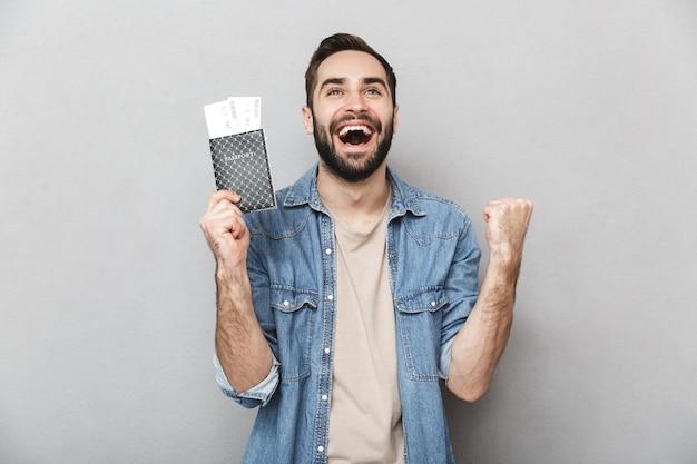 Heureux homme gai portant chemise isolé sur mur gris, tenant un passeport avec des billets d'avion, célébrant
