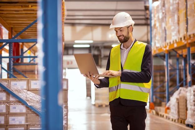 Heureux homme gai tenant un ordinateur portable lors de l'utilisation pour faire l'inventaire dans l'entrepôt