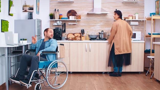 Heureux homme handicapé en fauteuil roulant à l'aide d'un ordinateur portable dans la cuisine. homme parlant en vidéoconférence. homme d'entreprise avec handicap handicap handicapé paralysie difficultés à travailler après accident ayant inter