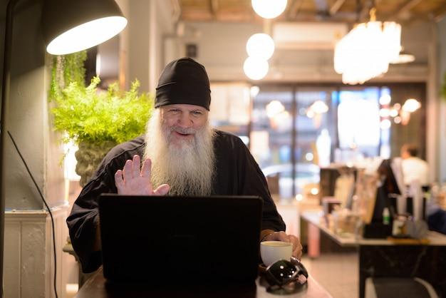 Heureux homme hipster barbu mature appel vidéo tout en utilisant un ordinateur portable au café