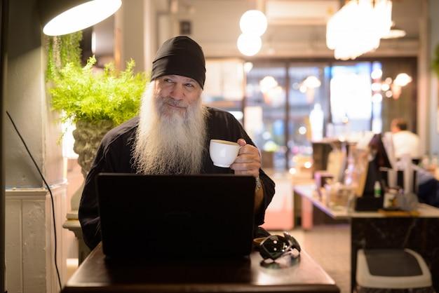 Heureux homme hipster barbu mature pensant tout en utilisant un ordinateur portable au café