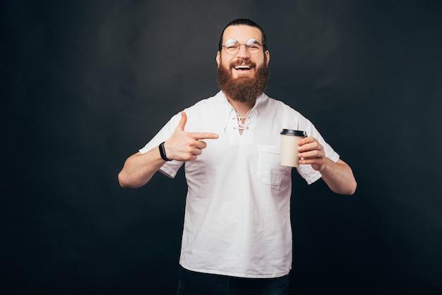 Heureux homme hipster barbu souriant et pointant sur une tasse de café en papier pour aller