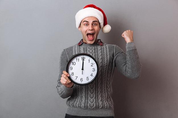 Heureux homme hurlant en pull et chapeau de noël tenant une horloge et se réjouir