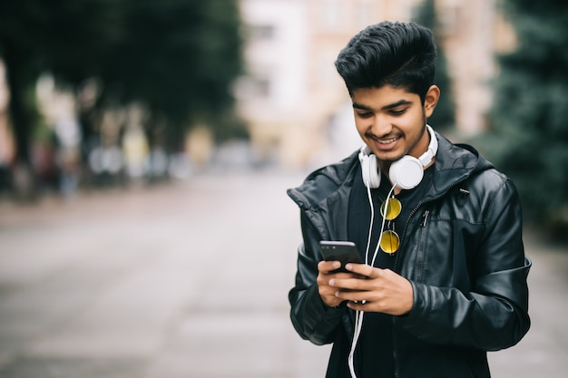 Heureux homme indien marchant et en utilisant un téléphone intelligent pour écouter de la musique avec des écouteurs