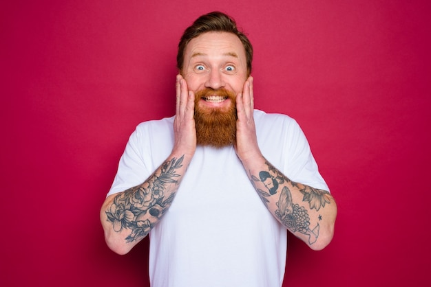 Heureux homme isolé avec barbe et t-shirt blanc