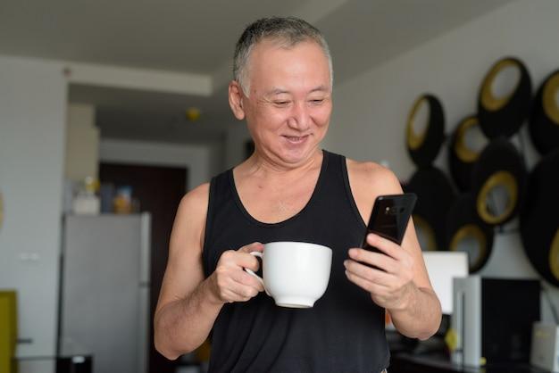 Heureux homme japonais mature, boire du café tout en utilisant le téléphone à la maison