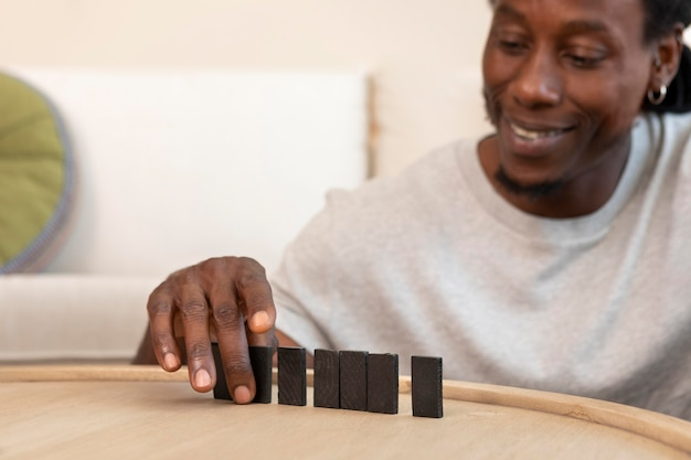 Heureux homme jouant avec des pièces de domino