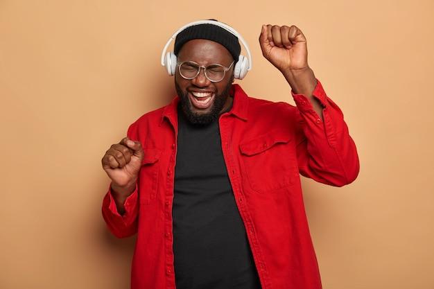 Heureux homme joyeux avec des poils lève les mains et apprécie les bonnes vibrations de la chanson préférée