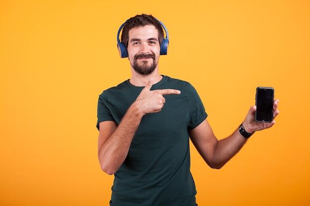 Heureux homme joyeux portant des écouteurs et pointant sur son smartphone isolé sur fond orange en studio.