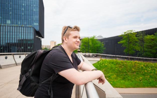 Heureux homme marchant et relaxant dans le parc de la ville moderne. homme posant à l'extérieur. concept de voyage et de vie active.