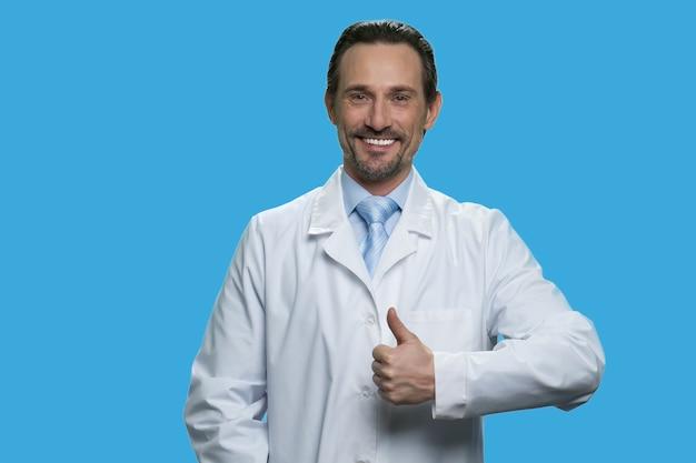 Heureux homme médecin mature montre le pouce vers le haut. un joyeux médecin caucasien d'âge moyen montre un signe isolé sur fond bleu.