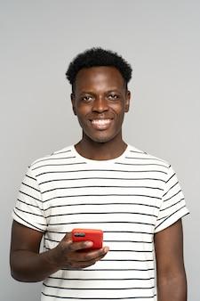 Heureux homme millénaire africain dans des verres, tenant un téléphone mobile, isolé sur fond gris studio