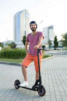Heureux homme monte un scooter électrique dans le parc