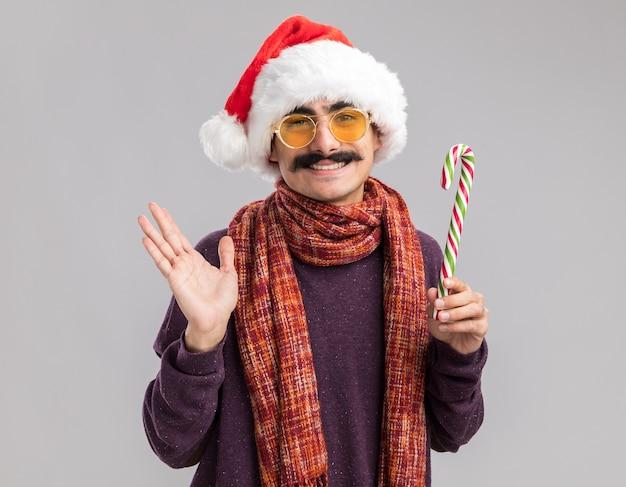 Heureux homme moustachu portant un bonnet de noel et des lunettes jaunes avec une écharpe chaude autour du cou tenant une canne en bonbon souriant joyeusement debout sur un mur blanc