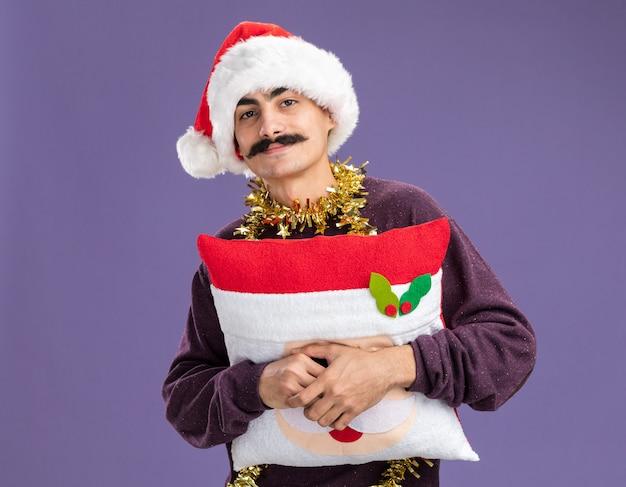 Heureux homme moustachu portant un bonnet de noel de noël avec des guirlandes autour du cou tenant un oreiller de noël avec un sourire sur le visage debout sur un mur violet