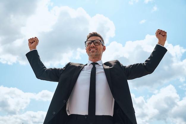 Heureux homme mûr en costume complet gardant les bras levés tout en se tenant devant le ciel bleu à l'extérieur