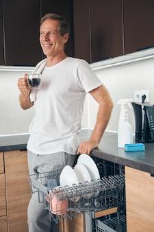 Heureux homme mûr et gentil gardant le sourire sur son visage tout en savourant le café du matin à la maison