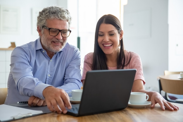 Heureux homme mûr joyeux et jeune femme assise à un ordinateur portable ouvert, regardant l'affichage, regardant le contenu sur une tasse de café et rire