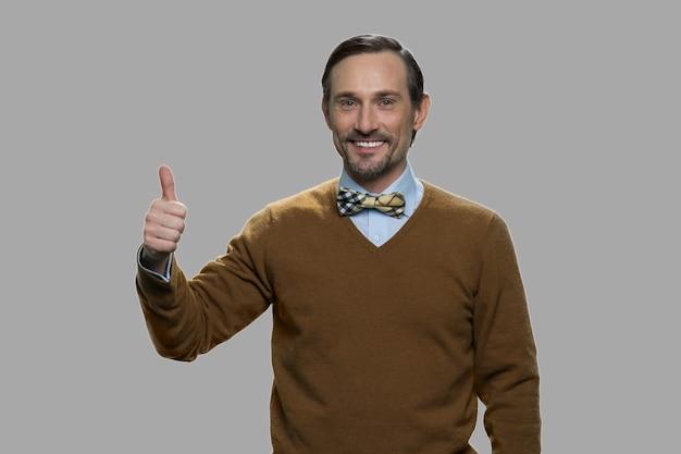 Heureux homme mûr montrant le pouce vers le haut. portrait de beau mec caucasien avec le pouce vers le haut signe sur fond gris.