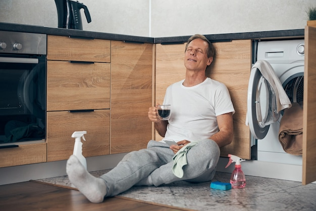 Heureux homme mûr ravi en gardant les yeux fermés alors qu'il était assis par terre dans la cuisine avec une boisson chaude