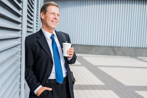 Heureux homme mûr avec une tasse de café en plein air