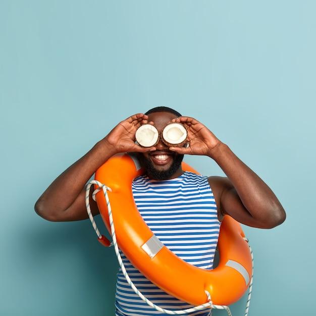 Heureux homme musclé barbu heureux posant avec des articles de plage