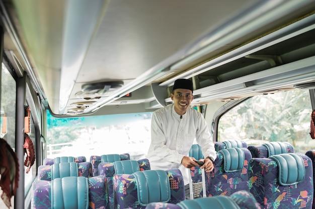 Heureux homme musulman asiatique faisant le voyage de retour dans sa ville natale en prenant un bus