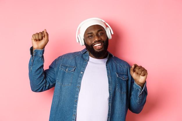 Heureux homme noir dansant et écoutant de la musique dans des écouteurs, souriant gai, debout dans des vêtements streetstyle sur fond rose