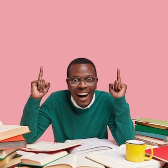 Heureux homme noir étonné en points de saut vert avec les deux index, a le sourire à pleines dents, entouré de nombreux livres