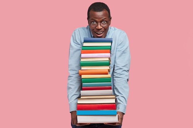 Heureux homme noir satisfait tient de nombreux livres dans les mains, regarde positivement, habillé en chemise formelle