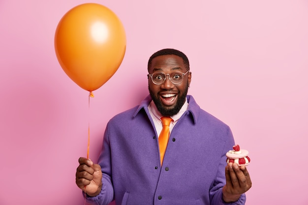 Heureux homme noir souriant tient ballon à air et petit petit gâteau, va féliciter un collègue avec anniversaire, a la bonne humeur