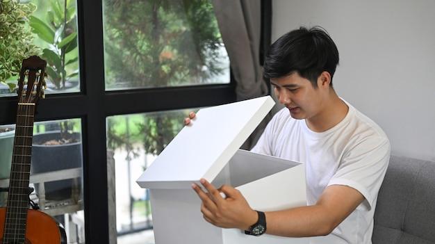 Heureux homme ouvrant une boîte-cadeau tout en étant assis sur un canapé à la maison.