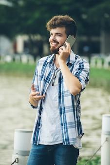 Heureux homme parle à sa petite amie au téléphone, debout à l'extérieur