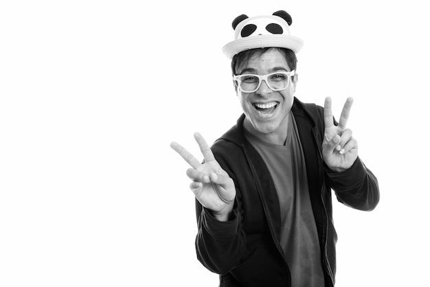Heureux homme persan souriant et donnant le signe de la paix avec les deux mains tout en portant un chapeau mignon et des lunettes jaunes