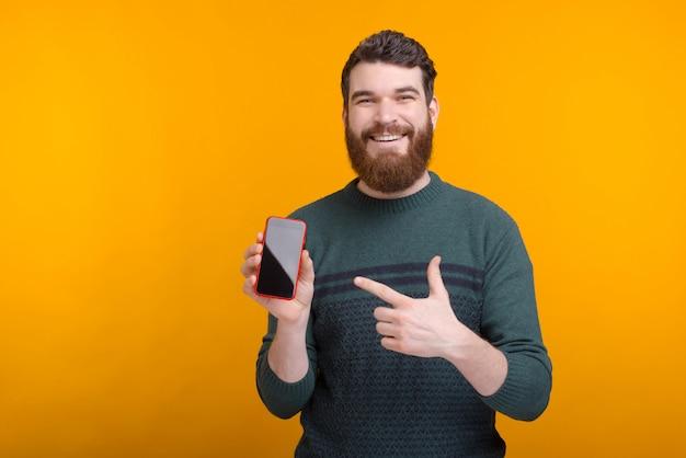 Heureux homme portant une barbe tient son téléphone et le pointe du doigt.