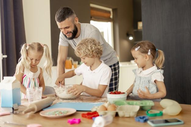 Heureux homme positif cuisiner avec ses enfants