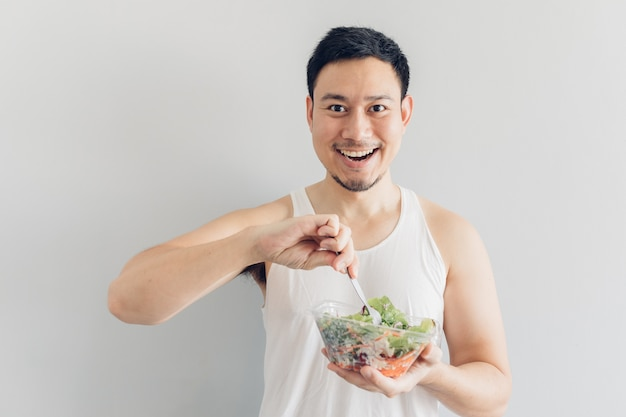 Heureux homme présente un repas de salade saine.
