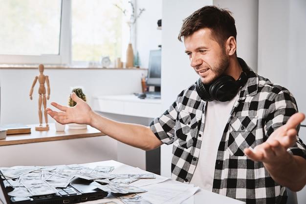 Heureux homme profiter de nombreux billets en dollars sur l'ordinateur portable faire de l'argent concept