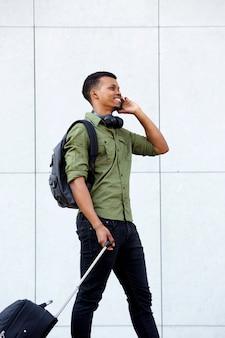 Heureux homme qui marche avec valise et téléphone