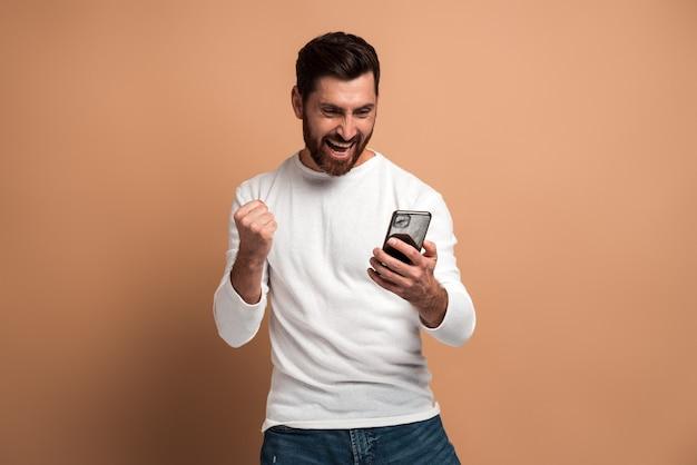 Heureux homme ravi avec une barbe regardant le smartphone et souriant faisant un geste oui, célébrant la victoire ou une bonne affaire. studio intérieur tourné isolé sur fond beige