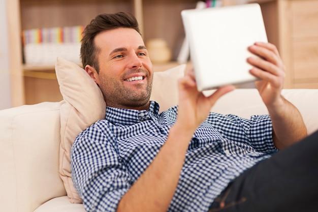 Heureux homme reposant sur un canapé avec tablette numérique