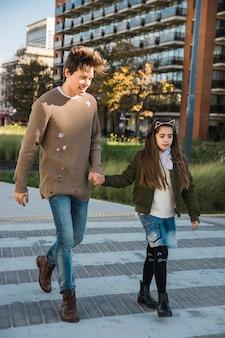 Heureux homme avec sa fille marchant ensemble sur le trottoir