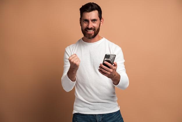 Heureux homme satisfait avec barbe tenant un smartphone et souriant faisant un geste oui, célébrant la loterie en ligne ou la victoire gratuite. studio intérieur tourné isolé sur fond beige